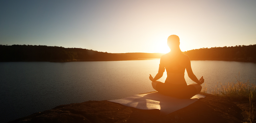 Silhouette of healthy woman is practicing yoga at mountain lake during sunset.